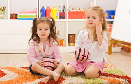 Two little girls holding in their hands piggybanks and sitting on the floor photo