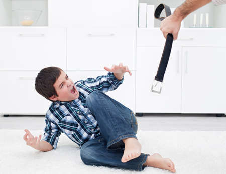 Strict father punishing his son with a belt photo