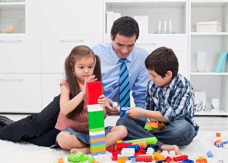 Happy father playing with his children after the working time Stock Photo