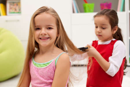 Little girl having her daily beauty routine - combing hair
