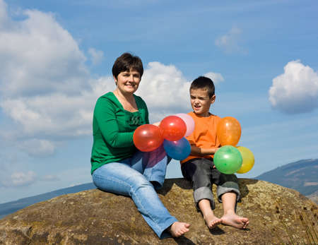 Beautiful woman and her son sitting on the stone with balloons in their hands Stock Photo - 17480153