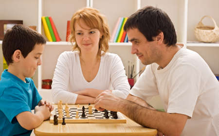 Father and his son playing chess meantime the young beautiful woman smiling photo
