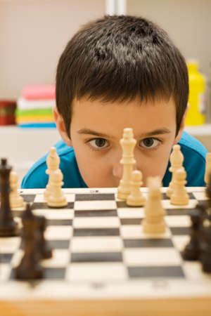 Boy looking at piece of chess photo