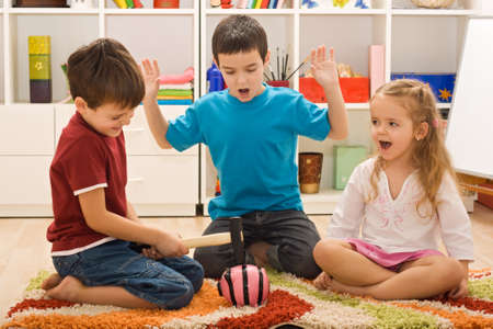Angry boy try to break the pink piggybank and the other two children looking frightened Stock Photo - 17480159