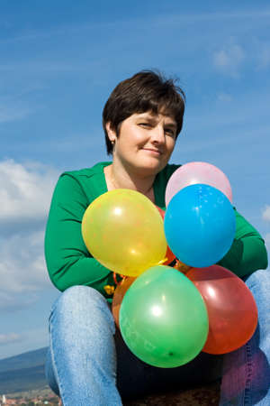 Beautiful woman sitting on the stone with balloons in her hand