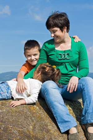 Beautiful woman and her happy children sitting on the stone