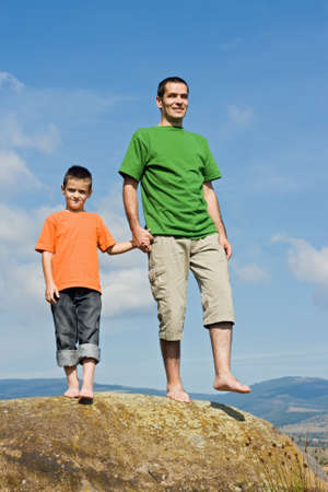 Father and his son standing on the stone and holding eatch others hands