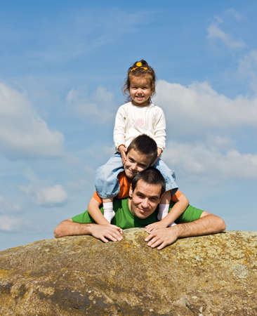 Father and his happy children leaning on the stone Stock Photo