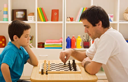Father and his son playing chess photo