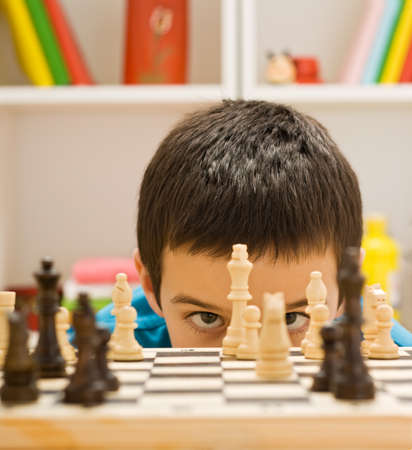 playing chess: Boy looking at piece of chess