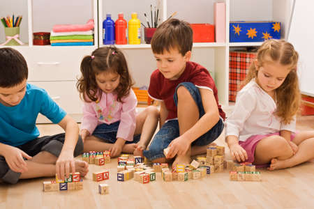 Children playing with blocks on the floor Stock Photo