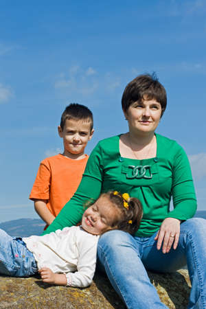 Beautiful woman and her happy children sitting on the stone Stock Photo - 17505012