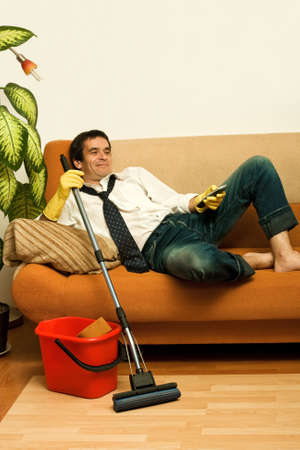 barefoot man: Happy man enjoying a tv show meantime of cleaning the room