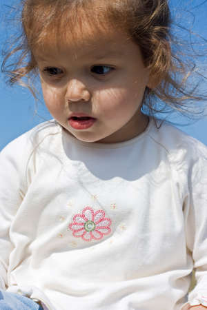 Beautiful little girl in white clothes looking down
