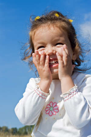 Beautiful little girl laughing puting the hands at her face Stock Photo