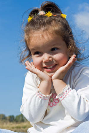 Beautiful little girl smiling and her hands are under jawl
