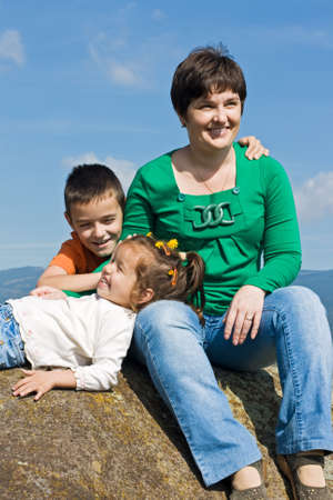 Beautiful woman and her happy children sitting on the stone Stock Photo - 17530552