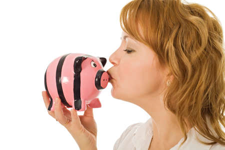 Young woman kissing a pink piggy-bank