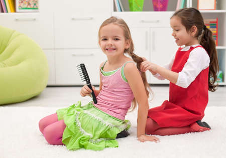 Happy little girls smiling meanwhile braiding of the plait Stock Photo - 17566123