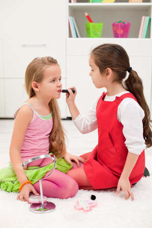 Little girl applying lipstick on her girlfriend's mouth Stock Photo - 17566121