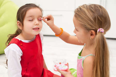 Little girl doing make-up to her girlfriend Stock Photo - 17566114