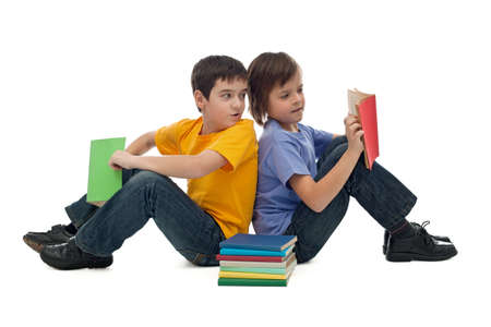 Two happy boys sitting on the floor and reading books Stock Photo