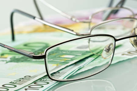 Three eyeglasses and currencies are on the table Stock Photo