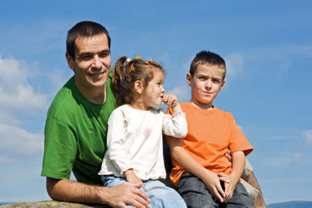 Father and his happy children sitting on the stone Stock Photo