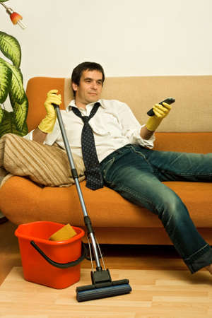 bad hygiene: Happy man enjoying a tv show meantime of cleaning the room