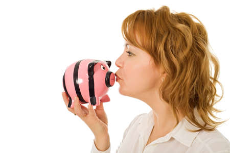 Young woman kissing a pink piggy-bank Stock Photo - 17668583