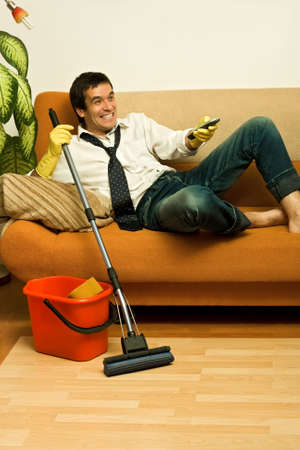 Happy man enjoying a tv show meantime of cleaning the room photo
