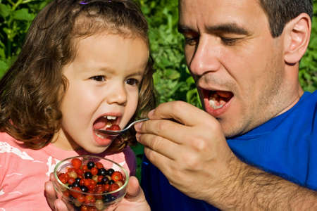 kids eating healthy: Father giving fresh fruits to his little girl