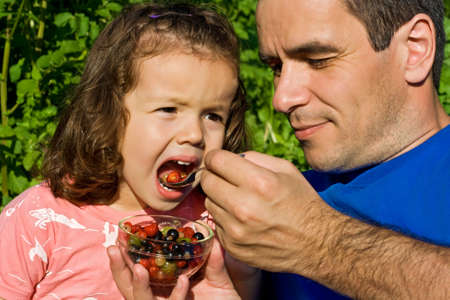 Father giving fresh fruits to his little girl