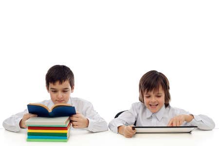 Two boys at the table, one of them reading traditional from the book the other playing on the tablet