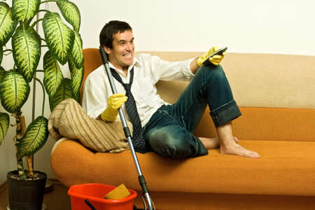 Happy man enjoying a tv show meantime of cleaning the room