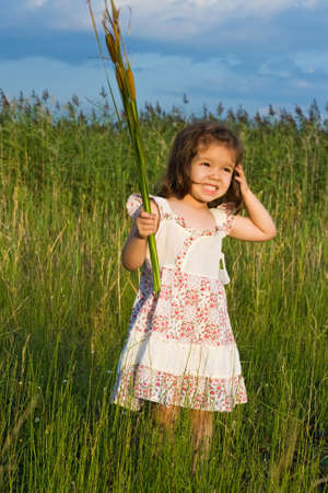 Little girl holding in her hands reeds