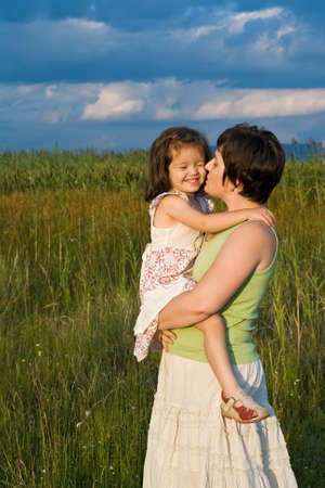 Beautiful young woman kissing her happy daughter Stock Photo