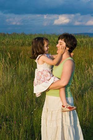caresses: Lovely girl fondling her mother face