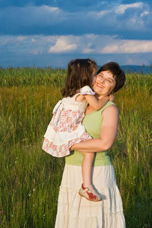 Little girl kissing her happy mother photo