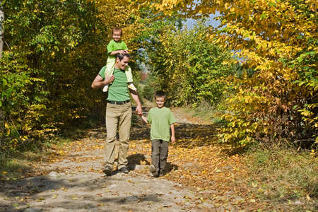Father and his two children walking on the path during autumn photo
