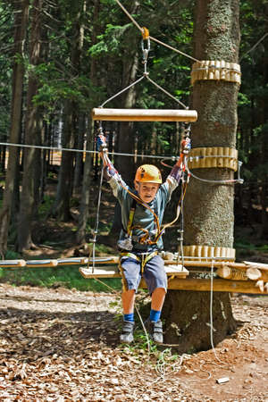Happy boy playing in an adventure park photo