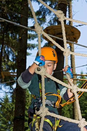 Boy climbing happily on the rope in an adventure park
