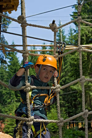 Happy boy climbing on rope in the adventure park Stock Photo