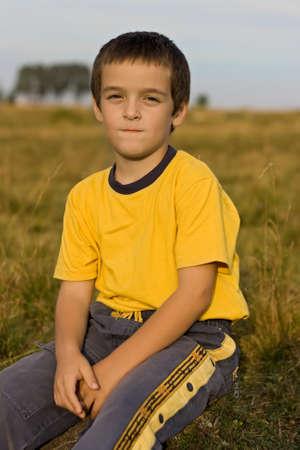 Happy boy sitting calmness on the grass Stock Photo