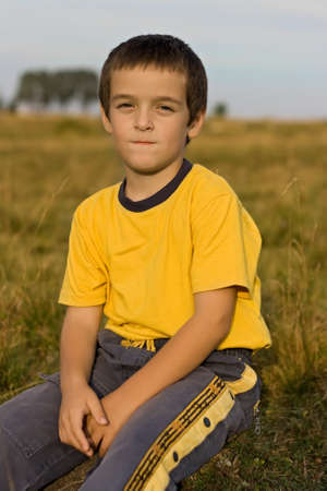 Happy boy sitting calmness on the grass Stock Photo