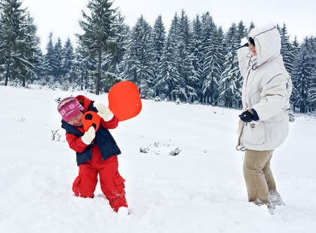 Happy woman playing with her daughter in winter time Stock Photo