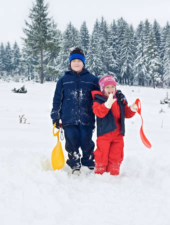 Two children staying in the snow, the boy embracing her sister Stock Photo