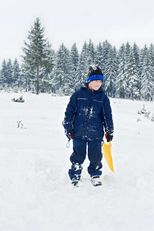 Happy boy staying in the snow Stock Photo
