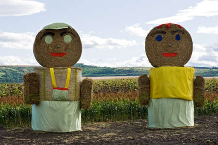 Huge straw couple staying on the field