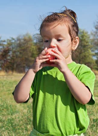 Beautiful little girl eating red apple Stock Photo